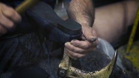 De oude schoenen van de schoenmakersreparatie stock videobeelden