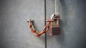 De oude sleutel van het roestslot met ketting op grijze cementmuur Het concept van de veiligheid stock foto's