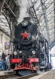 De oude Sovjet uitstekende zwarte retro trein met een rode ster bij het station in Lviv produceert stoom van de pijpen en passeng Stock Fotografie