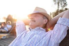 De oude Spaanse mens zit op bank, glimlachen, die de zomer van zonnige dag genieten stock afbeelding