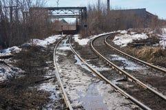 De oude spoorweg gaat naar een verlaten fabriek royalty-vrije stock foto
