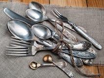 De oude staallepels, vorken en mes, verbindend met streng liggen op een dutje Royalty-vrije Stock Foto