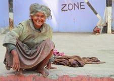 De oude tandenloze vrouw zit op de bestrating Stock Foto's