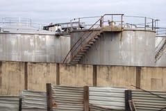 De oude tanks van de metaal industriële opslag met roestige die inspectieladders en de kleppen door een golfstaal worden omringd royalty-vrije stock foto