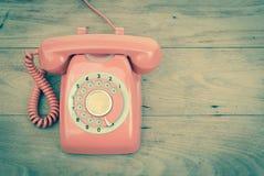 De oude telefoon van de telefoon roterende uitstekende retro stijl op houten lijstbovenkant Royalty-vrije Stock Foto
