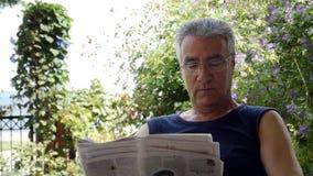 De oude teruggetrokken krant van de mensenlezing stock video