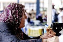 De oude Turkse vrouw eet stock afbeelding