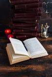 De oude uitstekende boeken met hard rood behandelen het leggen als een toren op een donkere houten lijst en één open boek royalty-vrije stock foto's