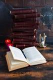 De oude uitstekende boeken met hard rood behandelen het leggen als een toren op een donkere houten lijst en één open boek royalty-vrije stock afbeeldingen