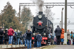 De oude uitstekende retro zwarte locomotief met rode ster kwam bij de post aan waar hij gefotografeerde passagiers en toeristen w Stock Foto