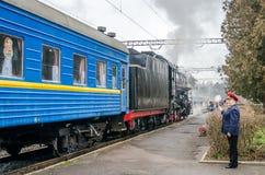 De oude uitstekende retro zwarte locomotief met rode ster kwam bij de post aan waar hij gefotografeerde passagiers en toeristen w Stock Afbeelding