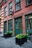 De oude uitstekende rode bakstenen commerciële bouw met restaurant binnen en groene houten deuren Stock Foto's