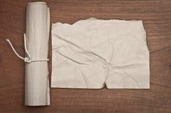 De oude verfrommelde document rol op houten lijst kan voor achtergrond gebruiken royalty-vrije stock afbeelding