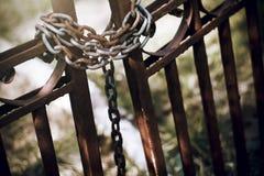 De oude verlaten poort wordt gesloten door een roestige ketting royalty-vrije stock afbeeldingen