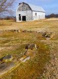 De oude Verlaten Schuur zit voorbij Amid Steenoverblijfselen van een Tijd stock foto's