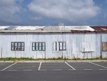De oude verlaten witte industriële bouw met roestend hersteld hersteld golfdak en ingescheept op vensters stock fotografie