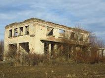 De oude vernietigde verlaten die bouw met struiken en struiken wordt overwoekerd royalty-vrije stock foto