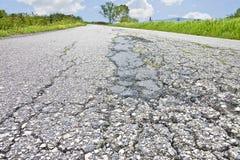 De oude versleten en gebarsten beschadigde achtergrond van het asfaltwegdek royalty-vrije stock fotografie