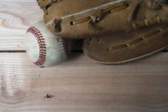 De oude versleten handschoen van het leerhonkbal en gebruikte bal op houten Stock Foto's