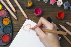 De oude verven, de potloden en de hand trekken een hart Royalty-vrije Stock Afbeeldingen