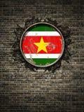 De oude vlag van Suriname in bakstenen muur Stock Foto's