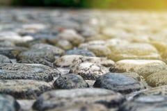 De oude vloer van Defocusedkiezelstenen op zonnestraal lichte achtergrond, close-up grote stenen royalty-vrije stock foto
