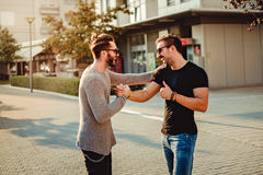 De oude vrienden komen en lachend terwijl het schudden van handen samen Stock Foto's