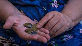 De oude vrouw bedelt voor aalmoes Close-up van geld en muntstukken ter beschikking van slechte vrouw royalty-vrije stock afbeelding