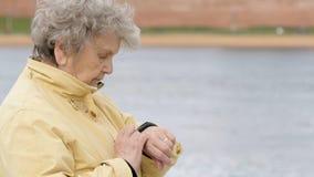 De oude vrouw bekijkt de drijver van de manchetgeschiktheid stock videobeelden