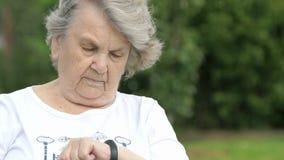 De oude vrouw bekijkt een drijver van de manchetgeschiktheid stock video
