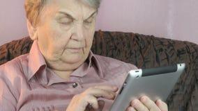 De oude vrouw die de zilveren tabletcomputer houden stock footage