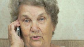 De oude vrouw die op een mobiele telefoon thuis spreken stock video