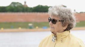 De oude vrouw in donkere glazen kijkt aan kant stock videobeelden