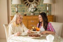 De oude vrouw heeft thee met een dochter stock foto