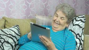 De oude vrouw houdt binnen een tabletcomputer stock footage