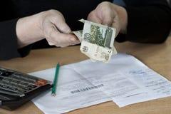De oude vrouw houdt de gelden Russische roebels in haar handen Stock Foto