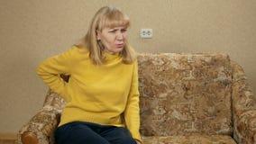 De oude vrouw kan niet van de laag wegens de pijn in de rug binnenshuis beklimmen Zij leunt en maakt een lumbale massage achterov stock videobeelden