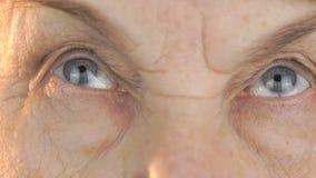 De oude vrouw kijkt de ogen in verschillende richtingen stock footage