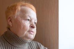 De oude vrouw kijkt uit het venster Stock Afbeelding