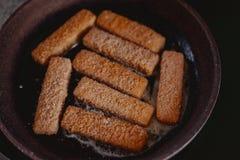 De oude vrouw kookt vissticks in pan royalty-vrije stock afbeelding
