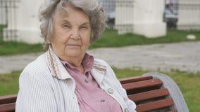 De oude vrouw met grijs haar zit in openlucht op een bank stock footage