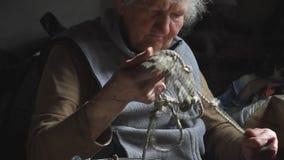 De oude vrouw met pijnlijke handen breit knopen op een kabel om een emmer in te verminderen goed, het leven in een verlaten dorp stock video