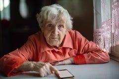 De oude vrouw neemt smartphonezitting bij de lijst over Stock Afbeelding