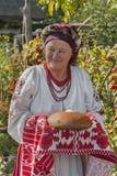 De oude vrouw in Oekraïens nationaal kostuum stelt gasten met brood in zout voor Royalty-vrije Stock Foto