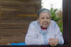 De oude vrouw op het balkon Stock Foto