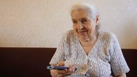 De oude vrouw schakelt het TV-kanaal met ver en glimlacht Oma ` die s op TV letten stock video