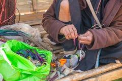 De oude vrouw van de heuvelstam maakt een ambachtsarmband Stock Foto