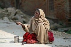 De oude vrouw vraagt liefdadigheid op de straat Stock Foto's