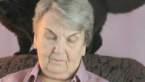 De oude vrouw zit bij een leunstoel naast een zwarte kat stock video