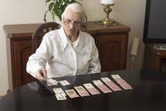 De oude vrouw zit bij een lijst en zet patience met kaarten stock foto's